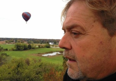 Mark Nelson gazes ahead as he pilots his hot-air balloon over the countryside near Smithfield. A balloon flown by his friend Reed Basley cruises in the distance.