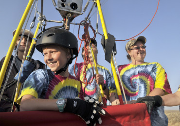 Bobby Bradley, 9, of Albuquerque is all smiles when he landed his ultralight hot air balloon after taking a 26 minute solo flight near Tome on Saturday, June 4, 2011.  Behind him in the tie-dyed shirts are his dad, Troy Bradley and mother, Tami Bradley.